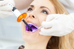 Dentista que usa la lámpara ULTRAVIOLETA de curado dental en los dientes del paciente foto de archivo
