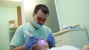 Dentista que usa la lámpara ULTRAVIOLETA de curado dental en los dientes del paciente almacen de video