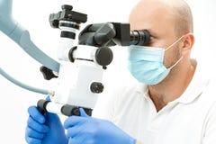 Dentista que usa o microscópio dental durante a inspeção Imagens de Stock Royalty Free