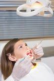 Dentista que usa o retractor da boca na menina Fotografia de Stock