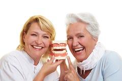 Dentista sonriente y mujer mayor