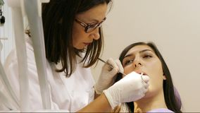 Dentista sul lavoro nell'unità dentaria con un paziente della giovane donna video d archivio