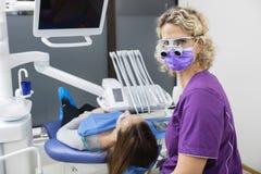 Dentista Wearing Loupes While che esamina giovane paziente in clinica Fotografia Stock