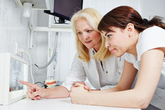 Dentista y assistand dental que miran imagen de la radiografía Foto de archivo