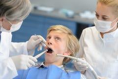 Dentista y ayudante con el paciente adolescente asustado Fotos de archivo libres de regalías