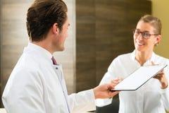 Dentista y enfermera con el tablero en clínica Imagen de archivo