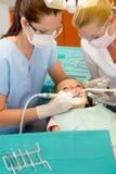 Dentista y enfermera que curan a la niña Foto de archivo