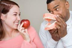 Dentista y mujer que sostienen una manzana y dientes falsos imágenes de archivo libres de regalías