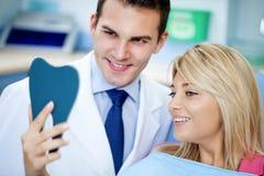 Dentista y paciente satisfecho con los dientes blancos Fotos de archivo