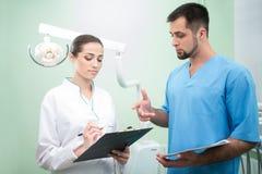 Dentista y su ayudante con los papeles foto de archivo