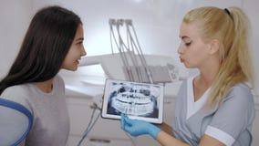 Dentista y tratamiento que elige paciente en una consulta con el equipamiento médico en el fondo almacen de metraje de vídeo