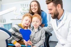 Dentistas com os meninos no officee dental foto de stock