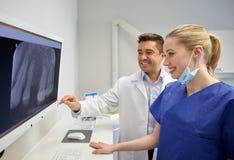 Dentistas com raio X no monitor na clínica dental imagem de stock