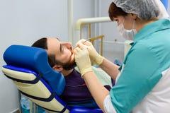 Dentistas de sexo femenino que trabajan en paciente masculino joven Oficina del ` s del dentista Imágenes de archivo libres de regalías