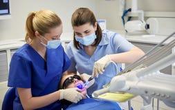 Dentistas de sexo femenino que tratan los dientes pacientes de la muchacha Foto de archivo libre de regalías