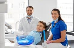 Dentistas e paciente da criança na clínica dental foto de stock