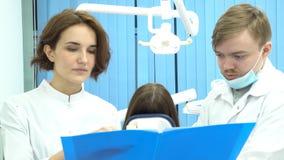 Dentistas fêmeas e masculinos que guardam um dobrador dos documentos que discutem o tratamento na frente do paciente na cadeira d fotografia de stock