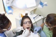 Dentistas que examinan los dientes del paciente en clínica dental fotografía de archivo libre de regalías
