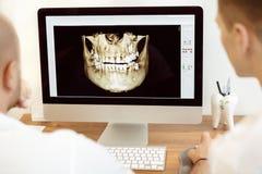 Dentistas y ayudante que discuten la radiografía imagen de archivo