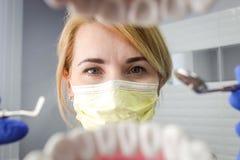 Dentiste au-dessus de la bouche patiente ouverte du ` s regardant dans des dents Soin oral photos stock