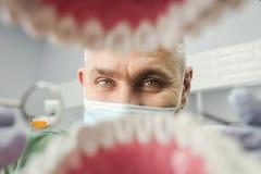 Dentiste au-dessus de la bouche patiente ouverte du ` s regardant dans des dents Soin oral I photos stock