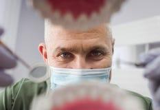 Dentiste au-dessus de la bouche patiente ouverte du ` s regardant dans des dents Soin oral I image libre de droits