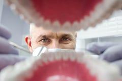 Dentiste au-dessus de la bouche patiente ouverte du ` s regardant dans des dents Soin oral I image stock