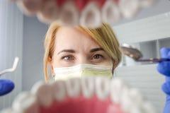 Dentiste au-dessus de la bouche patiente ouverte du ` s regardant dans des dents Soin oral I photos libres de droits