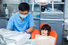 Dentiste au travail et son petit jeune patient gai Doc. asiatique photo stock