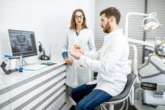 Dentiste avec l'assistant dans le bureau dentaire image libre de droits