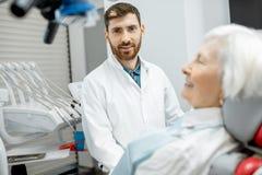 Dentiste avec la patiente supérieure de femme dans le bureau dentaire image stock