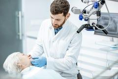 Dentiste avec la patiente supérieure de femme dans le bureau dentaire de chirurgie images stock