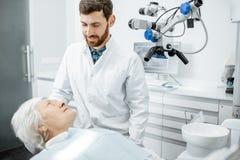 Dentiste avec la patiente supérieure de femme dans le bureau dentaire de chirurgie photos libres de droits
