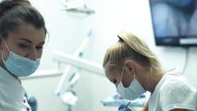 Dentiste avec les dents de examen de filles d'assistant dans la chaise de dentistes banque de vidéos