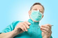 Dentiste avec un miroir et un crochet sur un fond vert - vue d'angle faible Images stock