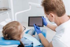 Dentiste compétent sensible donnant une petite conférence photographie stock libre de droits