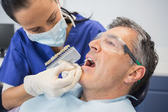 Dentiste comparant des dents blanchissant photographie stock libre de droits