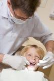 Dentiste dans la chambre d'examen avec le jeune garçon dans la présidence photo libre de droits