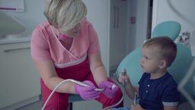Dentiste dans le masque médical et gants prêts à vérifier des tooths de peu de garçon insouciant s'asseyant dans la chaise femell banque de vidéos