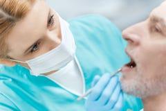 Dentiste dans le masque médical guérissant le patient mûr dans la clinique images stock