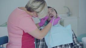 Dentiste de compétence dans le masque médical et gants vérifiant la bouche du patient à l'aide des outils médicaux Professionnel  banque de vidéos