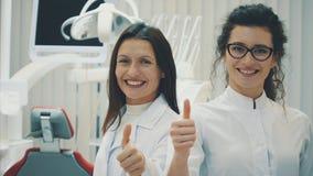 Dentiste de deux docteurs dans le bureau Belles jeunes femmes Position avec un petit peu un autre Regardez la caméra, fatiguée clips vidéos