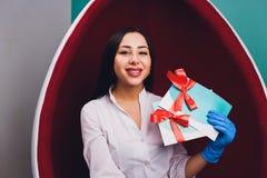 Dentiste de docteur expliquer l'implant des dents au patient dans la clinique dentaire illustration avec l'arc rouge photographie stock libre de droits