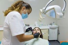 Dentiste de femelle adulte traitant les dents patientes de femme Concept de médecine, d'art dentaire et de soins de santé photographie stock