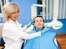 Dentiste de femme avec le patient mâle Photos stock