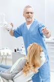 Dentiste de sourire supérieur dans l'uniforme avec le patient photo libre de droits
