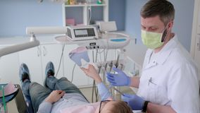 Dentiste Doctor à la visite de consultation dans la clinique de stomatologie de soins de santé banque de vidéos