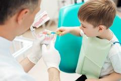 Dentiste enseignant les dents bruching de petit garçon dans la clinique dentaire photographie stock