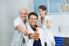 Dentiste et équipe dentaire tenant des pouces  image libre de droits