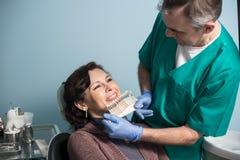 Dentiste et patient féminin vérifiant et sélectionnant la couleur des dents dans le bureau dentaire de clinique dentistry photos libres de droits